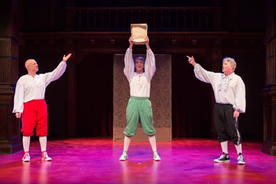 Spencer holds up the play manuscript as Martin and Tichenor flanking him point to it. All are wearing white puffy shirts, knee britches, white stockings, and tennis shoes: Martin in red pants and shoes, Spencer in green pants and shoes, Tichenor in black pants and shoes