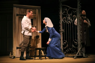 Claudio in white tunic and brown pants and boots holds hands with Isabella in white headscarf and long blue dress, standing up from kneeling, with Duke in green scarf covering his head listning through the gate. The jail door is behind Claudius, and there's a foot stool in front of him.