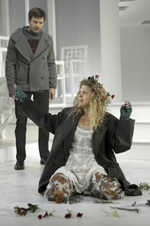 Laertes looks down on the distracted Ophelia, kneeling on the ground amid her flowers