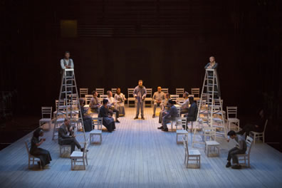 A platform with chairs, two ladders topped by George and Emily, their siblings seated in chairs below, his father, too, and toward the back of the stage other cast members sit around the choir director standing.