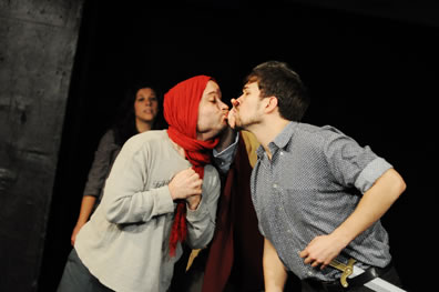 "thisbe in red scarf over his head puckers up as he seems to kiss Bottom between the ""chink"" (two spread fingers) in the wall"