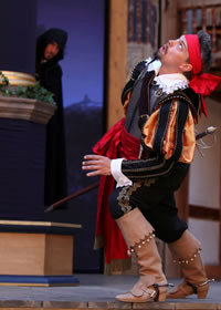 Parolles in cavilier clothes, puffy black and gold sleeves, red sash, tan high-heeled riding boots, red bandanna, reacts to a noise above him while a hooded man peers at him from behind a column in the background.