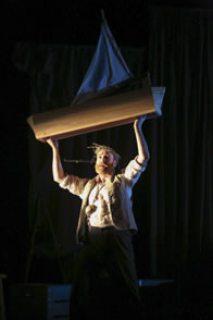 Prospero, in white shirt and rustic brown vest, bearded and wearing his thorn of twigs and a large necklace holds over his head a small wooden sailboat.