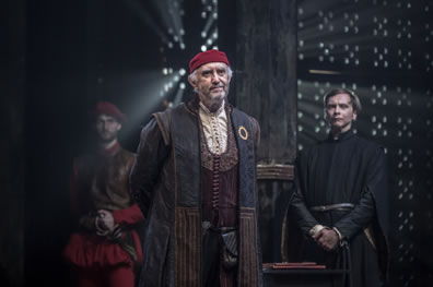 Shylock in bluish and redish robes, burgundy vest and white shirt plus red skullcap and hands behind his back, Prince in black robe behind him, guard in leather waiste coat and red breeches, light streaming through the grate of the back wall.