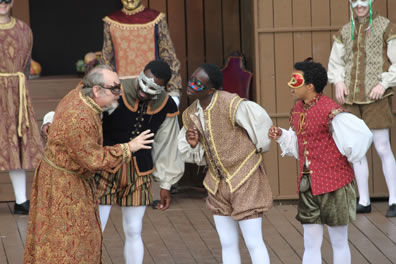 Capulet in long gold and red patterned robe with gold rope belt leans over to talk closely with Benvoloio in black waistcost and black, gold and green striped breeches, Mercutio in gold brocade waistcoat and breaches, and Romeo in red quilt wastecoat and green breeches. All are wearing masks, and all three young men are in white blousy shirts and white tights.