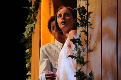 Juliet in a plain white nightgown and behind her Romeo in an Oxford shirt stand in a window with ivy vines on wood-paneled walls.