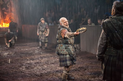 Duncan, in muted tartan kilt, holds out his crown to an opposing warrior with his back to us as other warriors watch; you can see the rain following, candles from one end of the stage in the background, and the audience sitting behind walls.