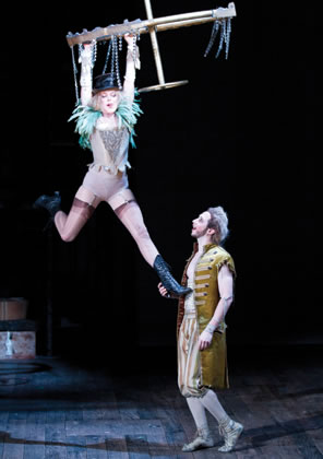 A fairy in vaudeville like lingerie hangs from a chandelier as Puck, in longcoat and britches, talks with her.
