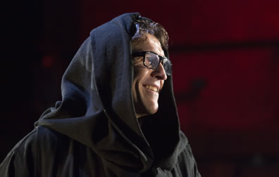 The Duke in a friars robe and hood, with dark-framed glasses and smiling off to the side.