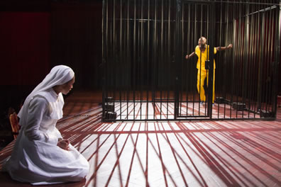 Isabella in nun's white habit on her knees, Claudio wearing yellow prison shirt and pants inside a jail cell, the bars casting shadows on the stage floor around the kneeling Isabella.