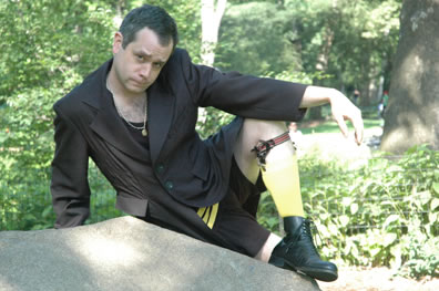 Malvolio lounges on a rock wearing a classic bathing suit, with yellow stockings and garter, underneath his stewards coat, and he still has his chain on