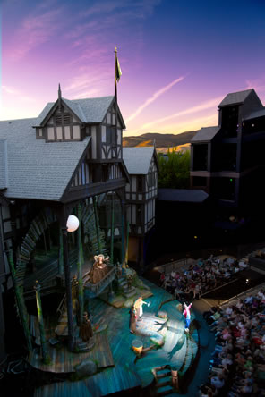 The timber-and-daub theater with a multilevel stage, the audience in an amphitheater, and sunset in the background