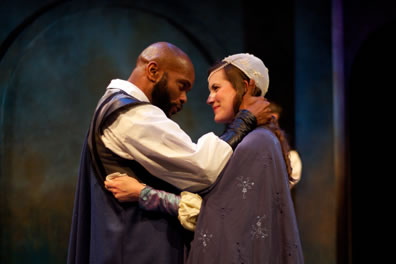 Othello with bald head and beard and blue cape embraces with Dessdemona in cap, blue cape and jewelled gown