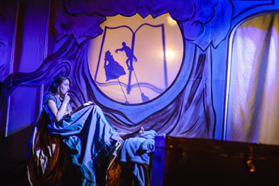 Imogen sitting in bed, wearing blue nightdress, book in her lap, and in window above her a shadow puppet of a man with long finges attackine a woman on an outline of a book. Iachimo's trunk is in the foreground of the photo