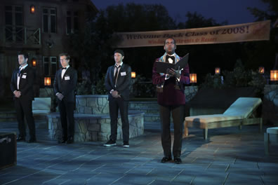 The king in red formal dinner jacket with open book, the lords in tuxedoes (Berowne's bowtie untied,Longaville with backward baseball hat and sneaker) on a flagstone pattio, with lounge chairs, and a banner welcoming class of 2008.