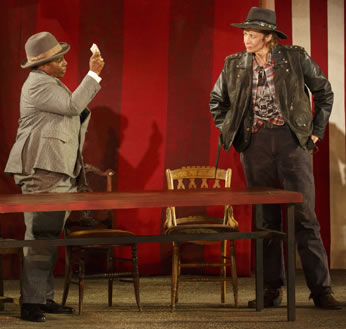 Baptista, wearing a tan suit and fedora, holds up a wad of cash before Petruchio in leather jacket, unbuttoned checkered shirt, death's head t-shirt, black jeans, and black outback hat. They are standing behind a table with chairs.