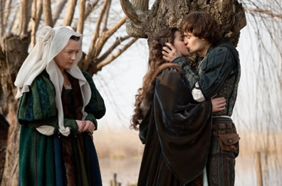 Nuse in green renaissance gown and white headdress with her head down and hands in worry position stands beside a kissing Juliet in black cloak and Romeo in blue