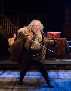 Falstaff swings his hacked sword arund, the motion obvious in his cloak as he stands leg separated, wearing a small shield in his left hand and an excited in his expression. A tavern wench listens in the background.