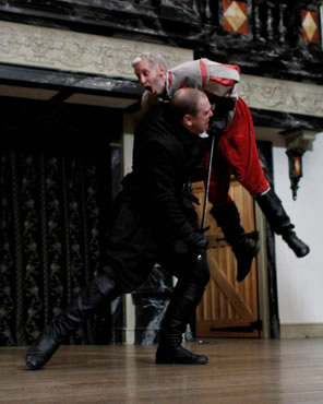 Richard in black stabs Somerset in red and is lifting him overhead with the sword.