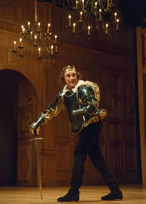 Richard in green armor, wearing crown, using his broadsword as crutch, with candle chandeliers hanging from the ceiling above