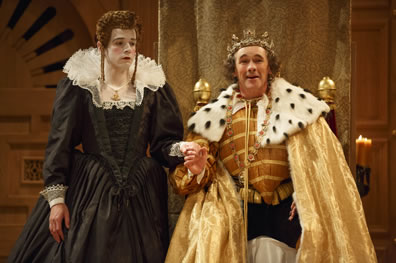 Richard in gold doublet, and shimmering gold cape with ermine coller and wearing a crown grinning and holding Lady Anne's hand. She in black dress with ruff coller looks wan