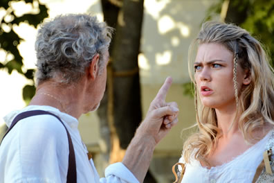 Prospero, in white shirt and burgundy suspenders, back right shoulder to the camera, points a finger in the face of Miranda, with two single braids in her straggly blond hair and a simple white blouse.