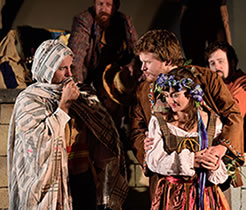 Production photo of Polixenes, scarf up to his face, talking with Florizel with his arms around Perdita as shepherds watch in the background.