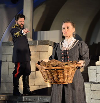 Production pic of Leontes pointing at Paulina holding a basket with the baby