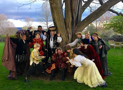 Around a tree in a park, various men and women in Elizabethan costumes with claws upraised close in on Falstaff sitting at the base of the tree.