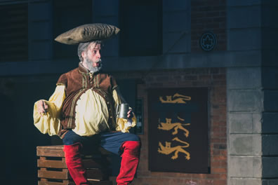 Falstaff, with protruding belly, sits on a crate and holds a tankard in his left hand, his right hand held out as if in regal posture with his mouth puckered in great pronouncement: he has a pillow on his head, and he's wearing his normal outfit of buckskin vest over yellow shirt, blue pants, and bright redk, knee-high boots. A banner of three royal lions hang on a brick wall in the background.