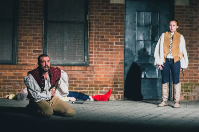 Hotspur kneeling on the ground, hands clutching his side, wearing red vest over white puffy shirt and tan pants, Hal standing off to the right, sword in her left hand, wearing buckskin vest over white puffy shirt, black jeans and gray knee-high boots, Falstaff lying in the background (red boots), sword next to him, all on a brick surface, and in the background the Carroll Park utility building, brick with black doors and windows.