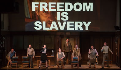 "The cast stand and crouch next to chairs, shouting, except Winston sitting, and O'Brien standing at the back in front of the office canteen door; overhead is a video image of the Brotherhood leader with ""Freedom Is Slavery"" in bold white letters sumperimposed over him"
