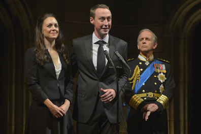Kate in black dress suit with white shirt, hands folded at her waist stands next to William in gray suit and tie with white shirt standing at a pair of microphones. Standing slightly behind them, Charles in dress uniform with medals, blue sash, and gold braids watches with his hands clenched at his waist.