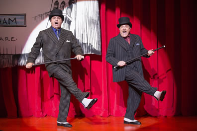 The two mobsters in classic mobster dark gray pinstripe suits but wearing tophats and holding canes kick out their right legs as they sing in a spotlight against a red curtain