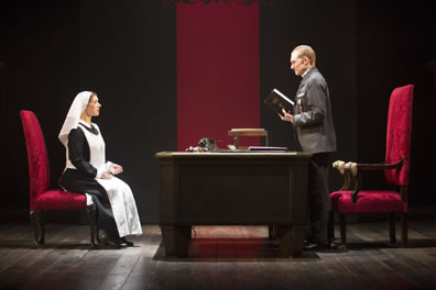 Isabella sits in a red chair across the desk from Angelo, standing, holding a Bible, large throne-like red chair behind him, and a red banner hanging down int he background