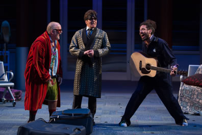 Toby in red robe, blue shurt, greetn shorts and wearing glasses, Malvolio in silk robe over vest, tie, white-colllared blue shirt and gray checked pants and wearing a night eye visor, and Feste, legs splayed as he's holding a guitar, wearing blue utility coveralls; luggage is strewn on the floor.