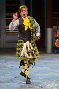 Malvolio steps forward daintly with finger pointed up as he wears a yellow and black plaid quilt, sash and hat, his gray vest and blue striped shirt, plus yellow stockings with cross-garters.