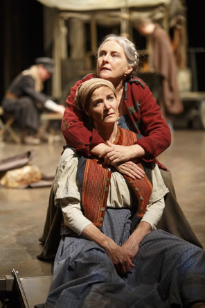 Mother Courage in red coat and looking off to the left behind Kattrin has her arms around the daughter's shoulder, Kattrin in Bohemian peasant dress and red vest looks off to the right, her hands dangling in her lap