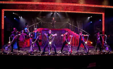 Lined up at the front of the stage, the biker stand with straddled legs, hands on the handlebars rising up from a single wheel and sporting a headlamp; a red double staircase leads to a platform where Leonato stands behind the rail; two showgirls stand on the left stair case. The silver gleamer curtain crosses the middle of the staircase, silver theater curtains are in the backdrop, and the stage floor is a pattern of black and white from the lighting.