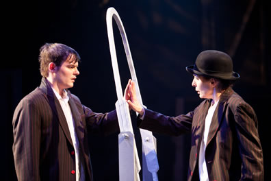 Sebastian and Viola touch palms through a white oval mirror frame, both in pinstripe jackets and white shirts, she in bowler hat.