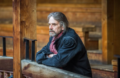 Jeremy Irons leaning with arms crossed on a balcony railing in a rustic theater