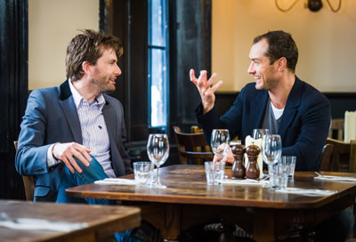 David Tennant and Jude Law (with hand up as if he's holding Yorick's skull) talk at a table in a pub