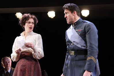 Beatrice holds a letter and looks amusingly at Benedick in uniform, who looks pained at the revelation in the letter