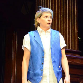 Julia in white work shirt, satin blue vest with subtle diamond pattern and lapels, and blue hair stands and looks to the side.