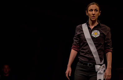 York, in dark purple shirt, black pants, a white rose on her shirt and a white sash with a bow at her belt, stands to one side of the photo, looking off to the side warily.