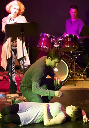 Lucrece lies sleeping on the floor with Tarquin bent over her, the narrator standing and the drummer behind his kit in the background