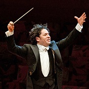 Dudamel, in tuxedo with black vest and white bowtie, hands upraise, baton in right hand, and hair flying.