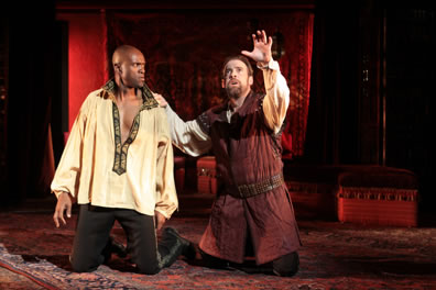 Othello and Iago kneeling, Iago with one hand raise, the other on Othello's shoulder