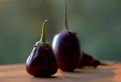 Eggplants standing up on outdoor table with deep focus creating a blurry depth