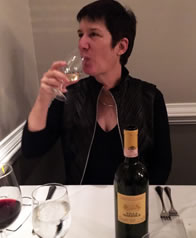 Sarah in a sexy black dress with high colar jacket sipping wine at a restaurant table